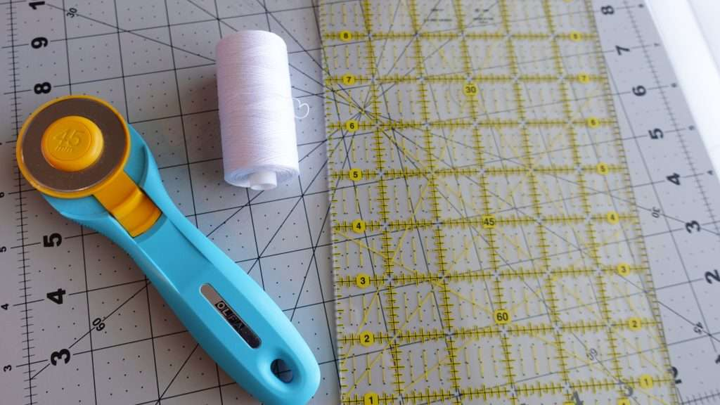 Quilting essentials, basic tools for quilting, rotary cutter, thread, quilting ruler
