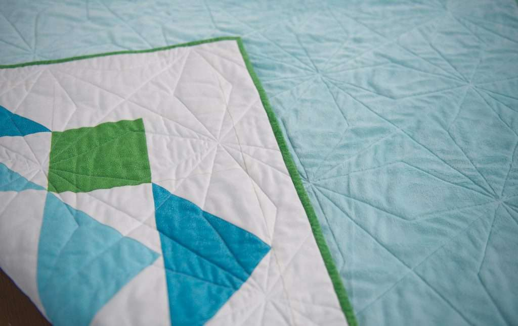 paradigm quilt pattern by homemade emily jabe is a great modern baby boy quilt pattern. If you're looking for an easy quilt pattern that features modern quilt pattern design, the Paradigm quilt pattern is perfect for you! this easy baby quilt was quilted with a fun geometric quilting design and backed with cozy minky fabric
