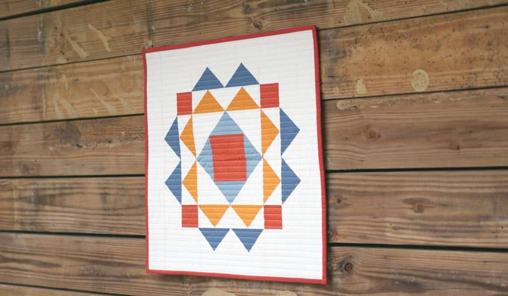 Modern Wall Hanging Quilt made from the paradigm quilt pattern by homemade emily jane. This is a modern quilt wall hanging pattern that features flying geese quilt blocks and an economy quilt block.