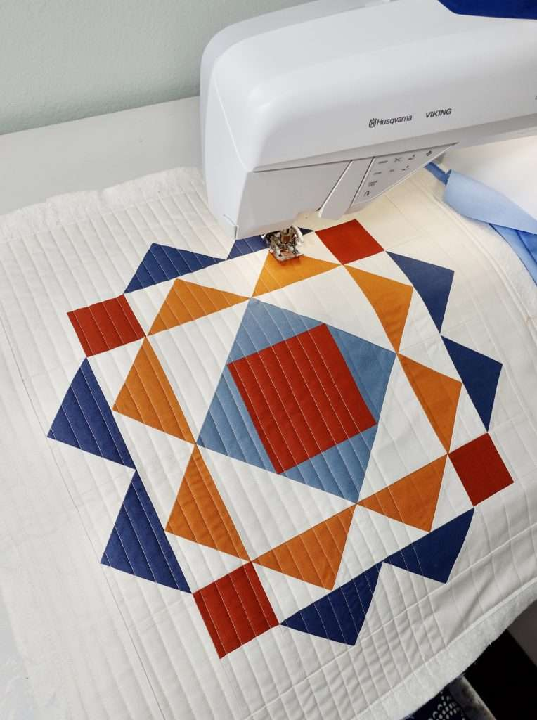 straight line quilting on the Modern Wall Hanging Quilt made from the paradigm quilt pattern by homemade emily jane. This is a modern quilt wall hanging pattern that features flying geese quilt blocks and an economy quilt block.