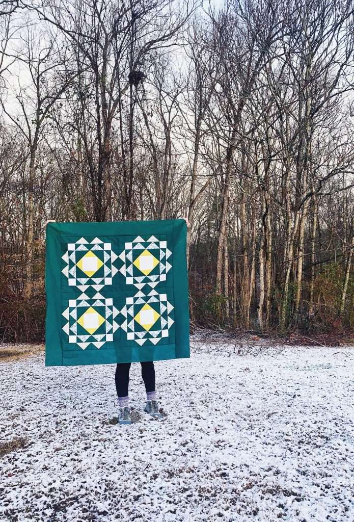Baby size sprightly quilt pattern with dark green background fabric
