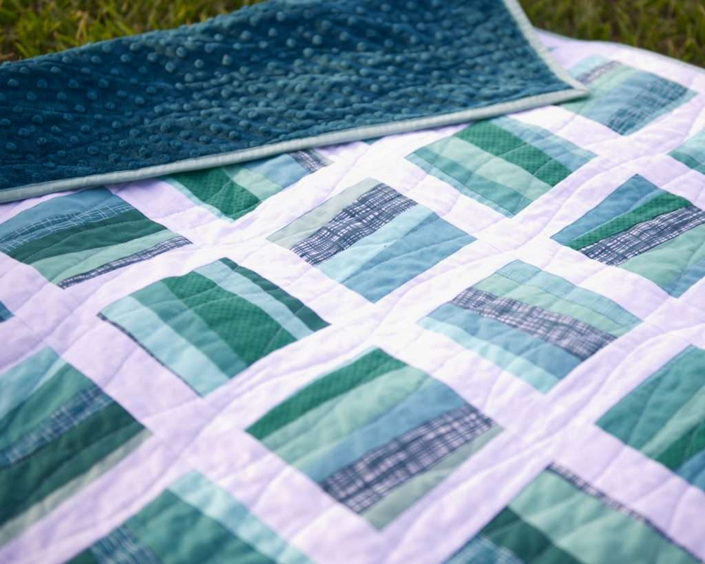 Wonky meander lines quilting on the improv block-based Stratus quilt